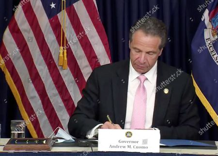 In this photo made from video provided by the office of New York Governor Andrew M. Cuomo, Gov. Cuomo, signs into law, in New York, a sweeping package of police accountability measures that received new backing following protests of George Floyd's killing. The laws signed by Cuomo, a Democrat, will ban police chokeholds, make it easier to sue people who call police on others without good reason, and set up a special prosecutor's office to investigate the deaths of people during and following encounters with police officers