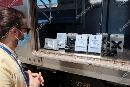 Contractor Andrea Brulicchio stands by several ultra violet lights used to kill the new coronavirus on subway cars at a maintenance facility in Corona section of Queens borough of New York on . The MTA is expanding the use of the devices to disinfect subway cars