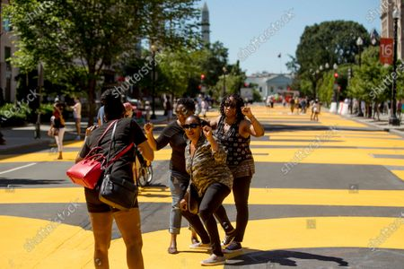 The Washington Monument is visible as sisters, from left, Pamela Bundy, Debbie Brown, and S.F. Powell of Prince George's County, Md., pose for a photographs on the words Black Lives Matter painted in bright yellow letters on part of 16th Street renamed Black Lives Matter Plaza a site of protests, near the White House in Washington. The protests began over the death of George Floyd, a black man who was in police custody in Minneapolis. Floyd died after being restrained by Minneapolis police officers
