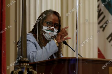 State Sen. Holly Mitchell, D-Los Angeles, chair of the Senate Budget and Fiscal Review Committee, wears a face mask and sits behind plexiglass as she and members of the committee grapple with state budget deficit, in Sacramento, Calif., . The state Legislature faces a deadline of midnight Monday, June 15, 2020 to pass the spending bill and submit it to Gov. Gavin Newsom