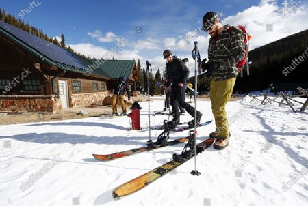 Graph, Garrett Akol, front, and Byron Thompson, both of Boulder, Colo., prepare to ski at Rocky Mountain National Park in Estes Park, Colo. Businesses involved in the outdoor industry, which has suffered several roundhouse blows from the new coronavirus, still see glimmers of hope for their endeavors because of the increase of interest in being outdoors