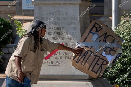 A man adjusts a protest sign at the feet of the 30-foot obelisk Confederate memorial known as the 'Lost Cause' on the square in Decatur, Georgia, USA, 12 June 2020. A DeKalb County judge on 26 June ruled that the Confederate monument in the Decatur square be removed by 26 June and relocated. Protesters have called for the removal of the Confederate obelisk, along with other Confederate statues and memorials across the South, amid protests following the death of George Floyd in police custody on 25 May in Minnesota.