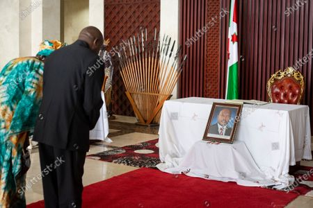 Burundi's president-elect Evariste Ndayishimiye, 2nd left, and his wife Angeline Ndayubaha, left, pay their respects in front of a photograph of the late President Pierre Nkurunziza, at the presidential palace in Bujumbura, Burundi . Burundi's constitutional court on Friday said president-elect Evariste Ndayishimiye should be sworn in as soon as possible, ending uncertainty created by the death of President Pierre Nkurunziza this week