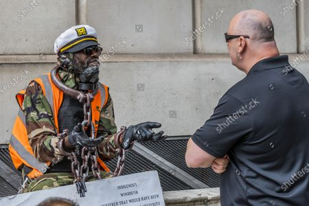 A black lives matter supporter in chains has a good natured chat with one of the prote3stors -0 Protesters, a mixed group of Tommy Robinson fans, football supporters and veterans meet to complain about the damage to statues, such as Churchills, by a minority of the Black Lives Matter protest a week ago.