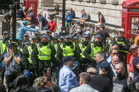 Stock Image of Riot police on standby as hundreds of  far-right activists gather around the Winston Churchill statue in Parliament Square which was covered up to protest after several statues were damaged during Black Lives Matter demonstrations.