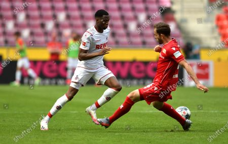 Stock Photo of Kingsley Ehizibue of 1. FC Koeln is challenged by Ken Reichel of 1.FC Union Berlin during the Bundesliga match between 1. FC Koeln and 1. FC Union Berlin at RheinEnergieStadion in Cologne, Germany, 13 June 2020.