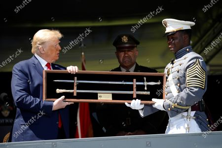 President Donald Trump is offered a class gift by Class President Cadet Joshua Phillips after speaking to over 1,110 cadets in the Class of 2020 at a commencement ceremony on the parade field, at the United States Military Academy in West Point, N.Y., . Superintendent of the United States Military Academy Lt. Gen. Darryl Williams is at center