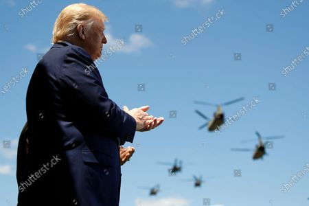 President Donald Trump and Superintendent of the United States Military Academy Lt. Gen. Darryl Williams applaud as Army helicopters fly over during the Class of 2020 at a commencement ceremony on the parade field, at the United States Military Academy in West Point, N.Y