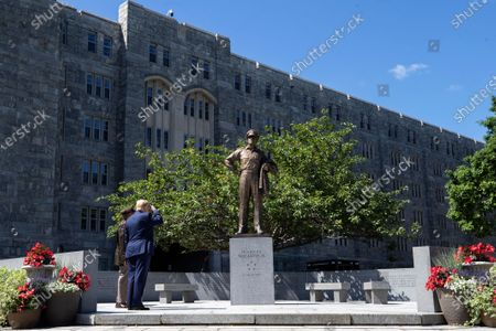 President Donald Trump, accompanied by Superintendent of the United States Military Academy Lt. Gen. Darryl Williams, salutes a statue of Gen. Douglas MacArthur, before speaking to over 1,110 cadets in the Class of 2020 at a commencement ceremony on the parade field, at the United States Military Academy in West Point, N.Y
