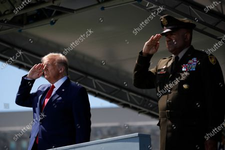 President Donald Trump, left, and United States Military Academy Lt. Gen. Darryl Williams, right, salute during a commencement ceremony on the parade field, at the United States Military Academy in West Point, N.Y