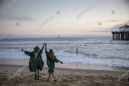 Sophia Strauss,17, left and Sarah Hoffmeister,17, right, celebrate following their drive-through graduation from Mira Costa High School in Manhattan Beach, CA, and a walk along the Strand path from Hermosa Beach Pier to the Manhattan Beach Pier, right, on Thursday, June 11, 2020. While Hoffmeister is headed to Westmont College in the fall, Strauss is undecided on her plans.