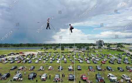 (EDITORS NOTE: image taken with a drone) High wire artists Nik Wallenda (left) and Blake Wallenda perform at Nik Wallenda's Daredevil Rally, billed as the world's first drive-in stunt show at Nathan Benderson Park.  The show, which runs on selected dates through June 21, features internationally known daredevil performers and is designed to be a safe event during the coronavirus pandemic, with the separation of spectator's vehicles according to social distancing guidelines.
