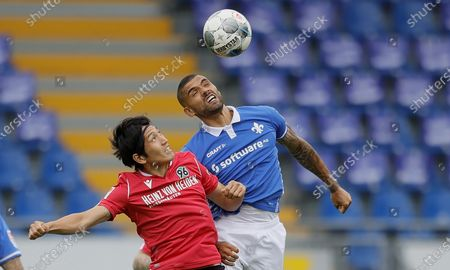 Hannover's Genki Haraguchi (L) and Darmstadt's Victor Palsson (R) in action during the German Bundesliga Second Division soccer match between SV Darmstadt 98 and Hannover 96 at Merck-Stadion in Darmstadt, Germany, 14 June 2020.