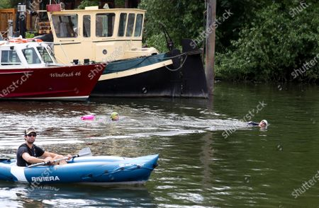 Stock Photo of Open water swimmers, Stuart Leigh & Fiona Buchanan swim in the River Thames, around Eel Pie Island, Twickenham, at a time when swimming pools are closed due to the coronavirus.  Watched by a man in a kayak