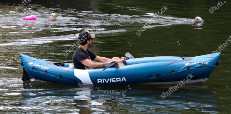Open water swimmers, Stuart Leigh & Fiona Buchanan swim in the River Thames, around Eel Pie Island, Twickenham, at a time when swimming pools are closed due to the coronavirus.  Watched by a man in a kayak.