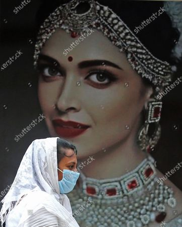 An Indian woman wears a mask as she walks in-front of the poster of Bollywood actress Deepika Padukone, as the city re-opens with strict guidelines in Bangalore, India, 14 June 2020.
