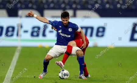 Daniel Caligiuri of Schalke is challenged by Mitchell Weiser of Leverkusen  (R) during the Bundesliga soccer match between FC Schalke 04 and Bayer 04 Leverkusen at Veltins-Arena in Gelsenkirchen, Germany, 14 June 2020.