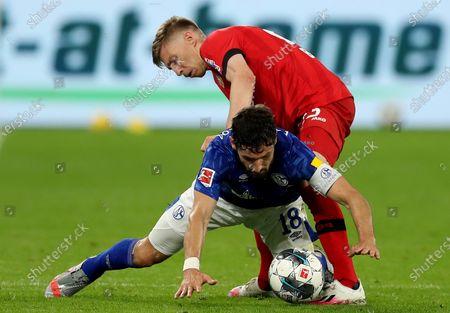 Daniel Caligiuri (front) of Schalke challenges Mitchell Weiser of Leverkusen during the Bundesliga soccer match between FC Schalke 04 and Bayer 04 Leverkusen at Veltins-Arena in Gelsenkirchen, Germany, 14 June 2020.