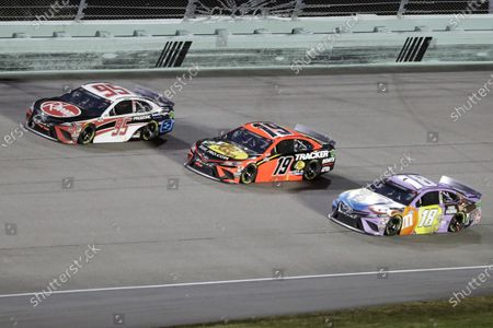 Christopher Bell (95), Martin Truex Jr. (19) and Kyle Busch (18) come through a turn during a NASCAR Cup Series auto race, in Homestead, Fla