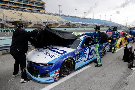 Crew members cover the car of Ty Dillon (13) during a weather delay at a NASCAR Cup Series auto race, in Homestead, Fla