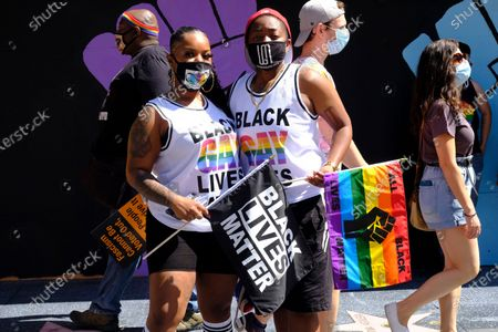 Stock Image of Stephanie Carr, left, and her wife Mia Carr, of Los Angeles, attend the All Black Lives Matter march, organized by black LGBTQ+ leaders,, in Los Angeles