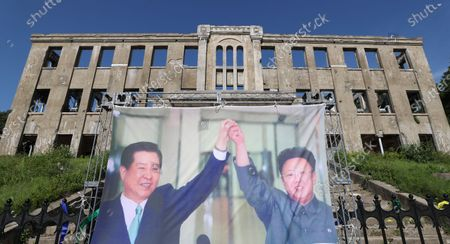 A large photo of late South Korean President Kim Dae-jung and late North Korean leader Kim Jong-il stands in front of the abandoned Workers' Party headquarters inside the demilitarized zone near Cheorwon, 88 kilometers northeast of Seoul, 15 June 2020. The photo has been put up to mark the 20th anniversary of the inter-Korean declaration that was reached following the historic first summit between the leaders of the two Koreas on 15 June 2000.