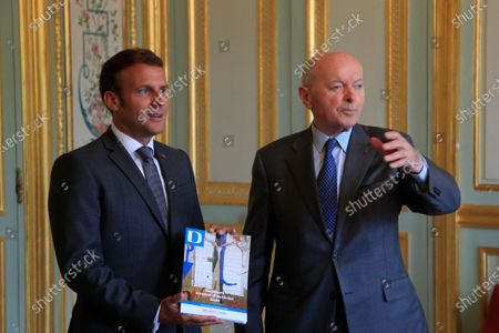 French President Emmanuel Macron holds the annual report he got from Jacques Toubon, the French Defender of the Rights, at the Elysee Palace in Paris
