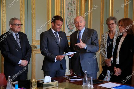 French President Emmanuel Macron, second left, holds the annual report he got from Jacques Toubon, third left, the French Defender of the Rights, at the Elysee Palace in Paris