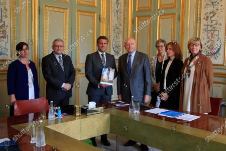 French President Emmanuel Macron, third left, holds the annual report he got from Jacques Toubon, fourth left, the French Defender of the Rights, at the Elysee Palace in Paris