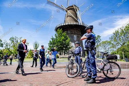King Willem-Alexander of the Netherlands chats with bicycle police officers during his visit to the Police Enforcement Team. The monarch met with the Extraordinary Investigating Officers (BOAs) and other law enforcement officials with whom the BOAs work closely together.