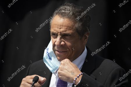 New York Gov. Andrew Cuomo removes a mask as he holds a news conference to announce the opening of a bicycle and pedestrian path across the Gov. Mario M. Cuomo Bridge, in Tarrytown, N.Y
