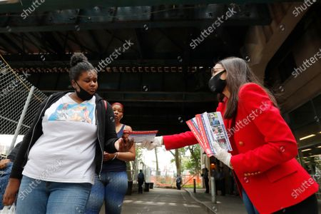 First-term U.S. Rep. Alexandria Ocasio-Cortez, D-New York, right, hands out leaflets explaining how to vote early or by absentee ballot to passersby at the Parkchester subway station in the Bronx borough of New York, in New York. Ocasio-Cortez is running against challenger and former journalist Michelle Caruso-Cabrera and others in New York's June 23 primary