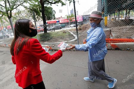 First-term U.S. Rep. Alexandria Ocasio-Cortez, D-New York, left, hands out leaflets explaining how to vote early or by absentee ballot to passersby at the Parkchester subway station in the Bronx borough of New York, in New York. Ocasio-Cortez is running against challenger and former journalist Michelle Caruso-Cabrera and others in New York's June 23 primary