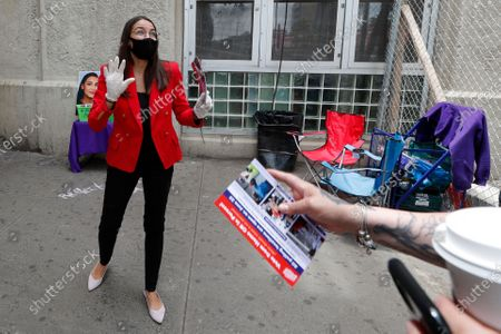 First-term U.S. Rep. Alexandria Ocasio-Cortez, D-New York, left, reacts as a passerby takes a leaflet explaining how to vote early or by absentee ballot at the Parkchester subway station in the Bronx borough of New York, in New York. Ocasio-Cortez is running against challenger and former journalist Michelle Caruso-Cabrera and others in New York's June 23 primary