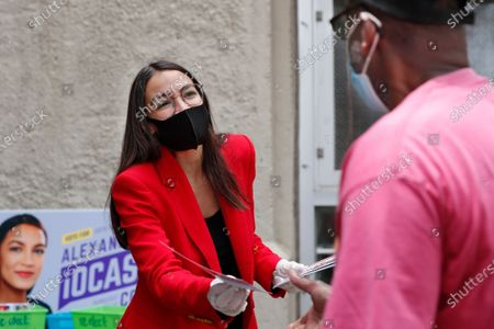 First-term U.S. Rep. Alexandria Ocasio-Cortez, D-New York, left, hands out leaflets explaining how to vote early or by absentee ballot to a pedestrian at the Parkchester subway station in the Bronx borough of New York, in New York. Ocasio-Cortez is running against challenger and former journalist Michelle Caruso-Cabrera and others in New York's June 23 primary