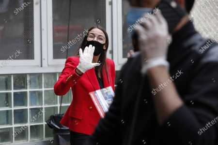 First-term U.S. Rep. Alexandria Ocasio-Cortez, D, New York, waves to passersby as she hands out leaflets explaining how to vote early or by absentee ballot to passersby as a man walks by on his cell phone at the Parkchester subway station in the Bronx borough of New York, in New York. Ocasio-Cortez is running against challenger and former journalist Michelle Caruso-Cabrera and others in New York's June 23 primary