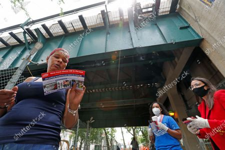 Woman left, looks at a leaflet about voting in the the upcoming New York primary election as first-term U.S. Rep. Alexandria Ocasio-Cortez, D, New York, far right, looks on after handing it out to pedestrians entering and leaving the Parkchester subway station in the Bronx borough of New York, in New York. Ocasio-Cortez is running against challenger and former journalist Michelle Caruso-Cabrera and others in New York's June 23 primary. Voters may use absentee ballots or vote early