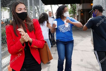 First-term U.S. Rep. Alexandria Ocasio-Cortez, D, New York, left, rubs hand sanitizer after handing out leaflets explaining how to vote early or by absentee ballot to people at the Parkchester subway station in the Bronx borough of New York, in New York. Ocasio-Cortez is running against challenger and former journalist Michelle Caruso-Cabrera and others in New York's June 23 primary. Ocasio-Cortez's workers bump elbows after completing the leaflefing effort as they left the subway station