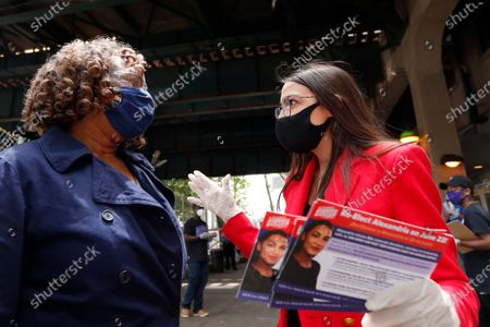 First-term U.S. Rep. Alexandria Ocasio-Cortez, D, New York, talks to Christine Richards while handing out leaflets explaining how to vote early or by absentee ballot to passersby at the Parkchester subway station in the Bronx borough of New York, in New York. Ocasio-Cortez is running against challenger and former journalist Michelle Caruso-Cabrera and others in New York's June 23 primary