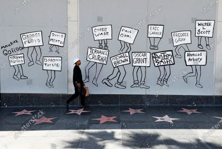 Man walks past a mural of black victims of police brutality on Hollywood Blvd., a day after a large protest march there, in Los Angeles. Protests continue to be held in U.S. cities over the death of George Floyd, a black man who died after being restrained by Minneapolis police officers on May 25