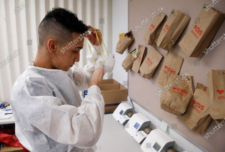 Berto Cortez, a CVS pharmacy technician, works in the coronavirus testing area set up by CVS at St. Vincent de Paul medical clinic, in Phoenix. The Arizona Department of Health Services posted on its website Monday another 1,104 cases of COVID-19 and eight additional deaths, bringing the statewide total number of coronavirus cases to 36,705 and related deaths to 1,194
