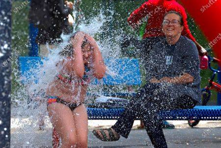 Katie Pawlowski, 8, left, plays in the spray park in the Squirrel Hill neighborhood of Pittsburgh with her mother Stephanie looking, . It was the first day that the City of Pittsburgh spray parks were reopened with Allegheny County now having been in the 'green' phase for two weeks