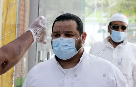 Shoppers have their temperatures checked before entering a mall in Jiddah, Saudi Arabia, . This was supposed to be Saudi Arabia's year to shine as host of the prestigious G20 gathering of world leaders. Instead, due to the coronavirus pandemic, the gathering this November will likely be a virtual meet-up. The impact of the coronavirus and low oil prices have forced a recalibration of Prince Mohammed bin Salman's ambitious plans to revamp Saudi society and its oil-dependent economy