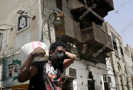 Worker, wearing a face mask as a precaution against the coronavirus, carries a load at Jiddah's historical district, in Jiddah, Saudi Arabia, . This was supposed to be Saudi Arabia's year to shine as host of the prestigious G20 gathering of world leaders. Instead, due to the coronavirus pandemic, the gathering this November will likely be a virtual meet-up. The impact of the coronavirus and low oil prices have forced a recalibration of Prince Mohammed bin Salman's ambitious plans to revamp Saudi society and its oil-dependent economy