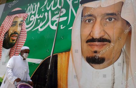 Man walks past a banner showing Saudi King Salman, right, and his son Crown Prince Mohammed bin Salman, outside a mall in Jiddah, Saudi Arabia, . This was supposed to be Saudi Arabia's year to shine as host of the prestigious G20 gathering of world leaders. Instead, due to the coronavirus pandemic, the gathering this November will likely be a virtual meet-up, stripping its host of the pomp that would have accompanied televised arrivals on Riyadh's tarmac