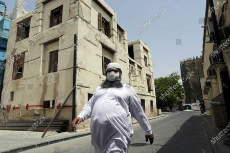 Worker, wearing a face mask as a precaution against the coronavirus, walks at Jiddah's historical district, in Jiddah, Saudi Arabia, . This was supposed to be Saudi Arabia's year to shine as host of the prestigious G20 gathering of world leaders. Instead, due to the coronavirus pandemic, the gathering this November will likely be a virtual meet-up. The impact of the coronavirus and low oil prices have forced a recalibration of Prince Mohammed bin Salman's ambitious plans to revamp Saudi society and its oil-dependent economy