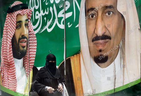Woman walks past a banner showing Saudi King Salman, right, and his Crown Prince Mohammed bin Salman, outside a mall in Jiddah, Saudi Arabia, . This was supposed to be Saudi Arabia's year to shine as host of the prestigious G20 gathering of world leaders. Instead, due to the coronavirus pandemic, the gathering this November will likely be a virtual meet-up, stripping its host of the pomp that would have accompanied televised arrivals on Riyadh's tarmac