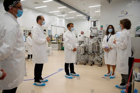 French President Emmanuel Macron, Thomas Triomphe, Executive Vice President of Sanofi Pasteur, and Paul Hudson, Chief Executive Officer of Sanofi, wearing protective face masks, visit an industrial development laboratory at the French drugmaker's vaccine unit Sanofi Pasteur plant in Marcy-l'Etoile, near Lyon, France, June 16, 2020.