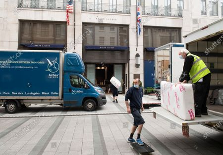 Shops in London gearing up for opening on the 15th June.Workers helping to prep Ralph Lauren on New Bond Street