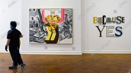 "Stock Photo of A visitor wearing a facemask and gloves next to (L) ""Serenade"", 2019, by David Salle and ""BECAUSE YES"", 2020, by Jack Pierson on the opening day of a new exhibition ""Art Basel at Ely House"" taking place at Galerie Thaddaeus Ropac in Mayfair. The commercial gallery has implemented social distancing guidelines for visitors for its reopening after coronavirus pandemic lockdown restrictions were relaxed by the UK government. The exhibition runs 16 June to 31 July 2020."